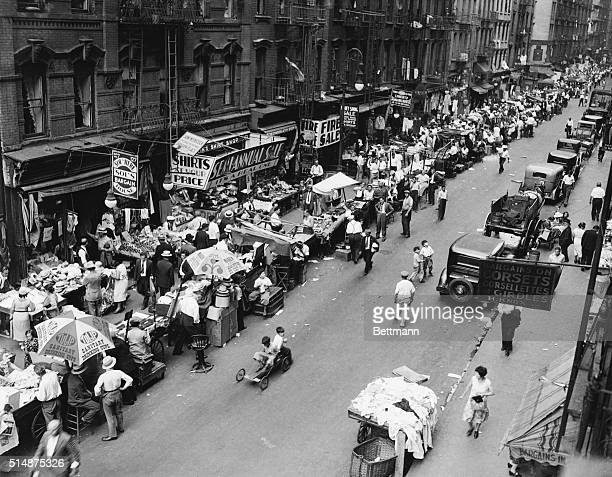 Vendors sell their wares from pushcarts on a street in New York's lower east side 1932