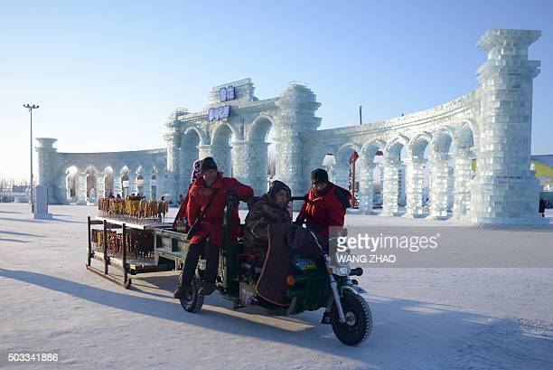 Vendors selling candied haws wait for customers at the China Ice and Snow World before the opening ceremony of the Harbin International Ice and Snow...