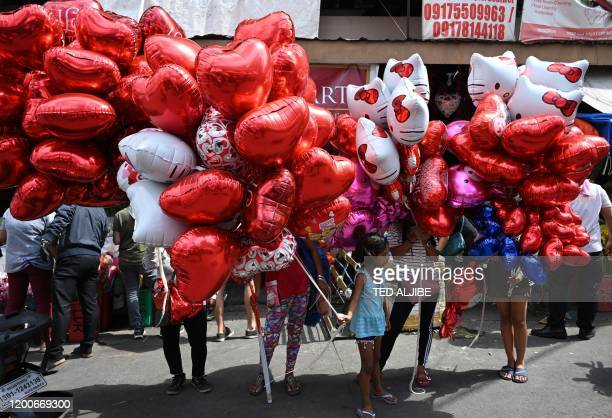 Vendors selling heartshaped ballons wait for customers on Valentine's day at a flower market in Manila on February 14 2020
