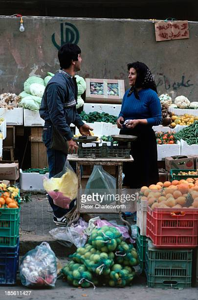 Vendors selling oranges and vegetables from carts in a small streetside market in West Beirut