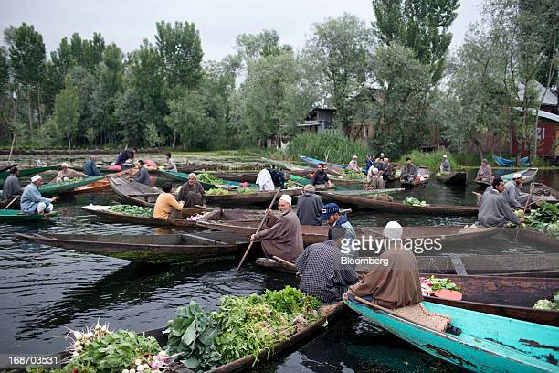 Vendors sells vegetables from their boats at a floating market on the Dal Lake in Srinagar India on Monday May 13 2013 Indian inflation eased to a...