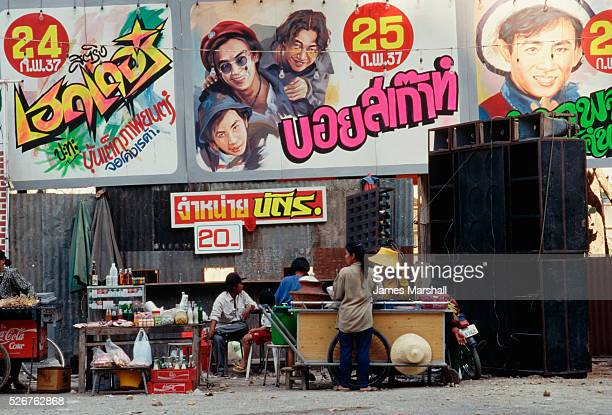 Vendors set up food stands underneath Thai movie billboards while speakers blare traditional Thai music | Location Petchaburi Thailand