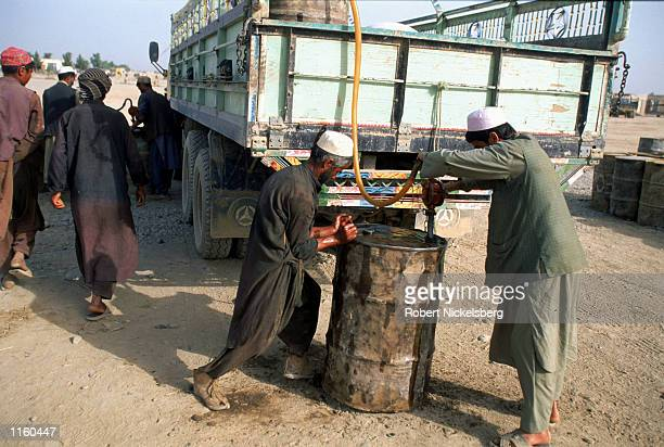 Vendors siphon gasoline from a truck from Tajikistan May 2001 in opposition-held terrirtory in Takhar province in northern Afghanistan. The...