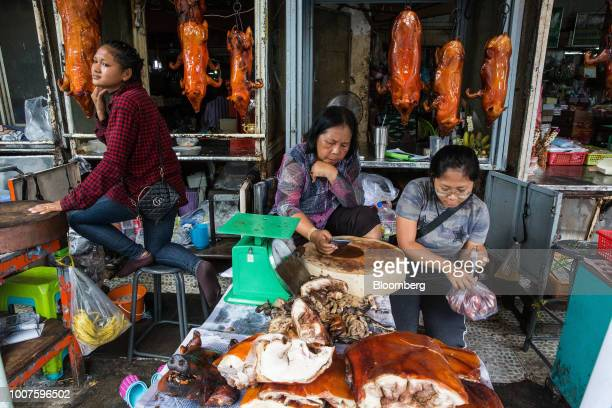 Vendors sit at a roasted pork stall at Orussey Market in Phnom Penh Cambodia on Friday July 27 2018 Cambodian Prime MinisterHun Senextended his...