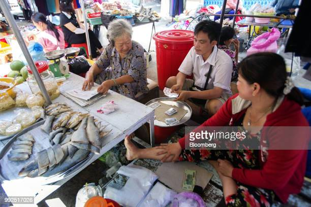 Vendors sit playing cards as they wait for customers at a market stall in Ho Chi Minh City Vietnam on Wednesday June 20 2018 For decades Vietnamese...