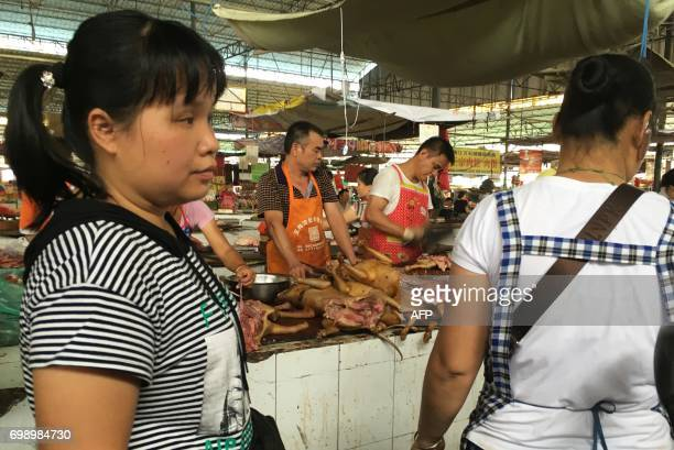 Vendors stand behind a pile of dog meat at the Nanqiao market in Yulin in China's southern Guangxi region on June 21 2017 China's most notorious dog...