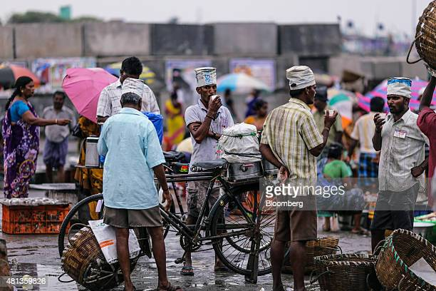 Vendors stand drinking at the Kasimedu fish market at the Royapurum fishing harbour in Chennai India on Wednesday July 15 2015 A banking system...