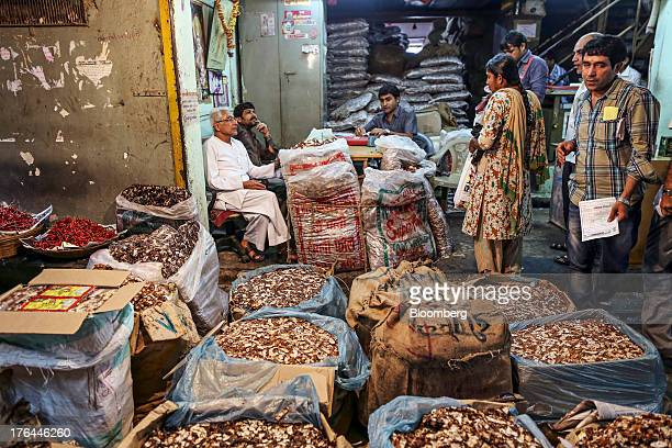 Vendors talk to customers as bags of tamarind sit on display at a store in the Vashi Agricultural Produce Market Committee wholesale market in Mumbai...