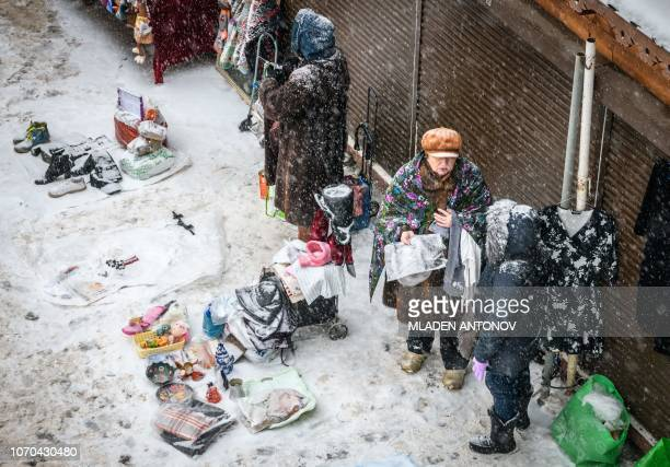 TOPSHOT Vendors talk under the snow at Izmailovo flea market in Moscow on December 9 2018