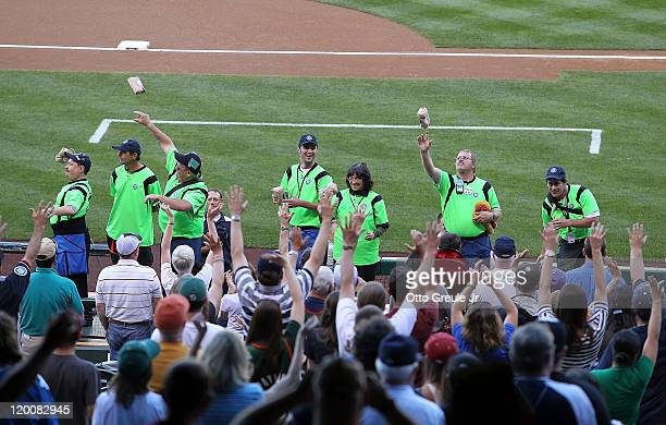 Vendors toss bags of peanuts to fans in honor of Rick Kaminski the vendor better known as 'The Peanut Man' prior to the game between the Seattle...