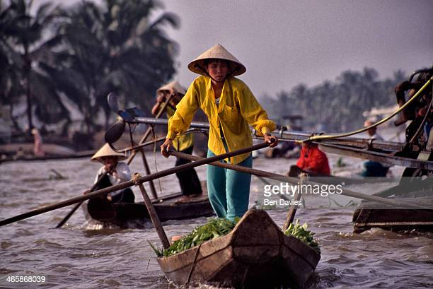 Vendors use sculls to row to Phung Hiep one of the world's largest floating markets situated at the confluence of seven canals in the Mekong Delta in...