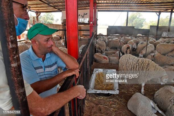 Vendors wait for costumers at a livestock market in the Algerian capital Algiers on July 12 ahead of Eid alAdha celebrations which might be cancelled...