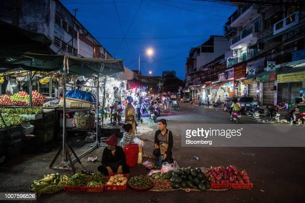 Vendors wait for customers at a roadside fruits and vegetables stall at night in Phnom Penh Cambodia on Sunday July 29 2018 Cambodian Prime...