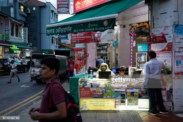 Vendors wait for customers at a stall selling mobile phone sim cards in the Little India area of Singapore on Wednesday June 13 2018 Tourism as well...