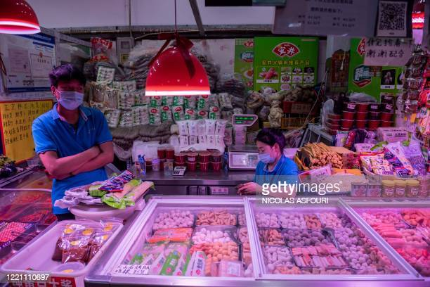 Vendors wait for customers at their stall selling frozen meat and seafood balls at a market in Beijing on June 20, 2020. - Tens of thousands of...