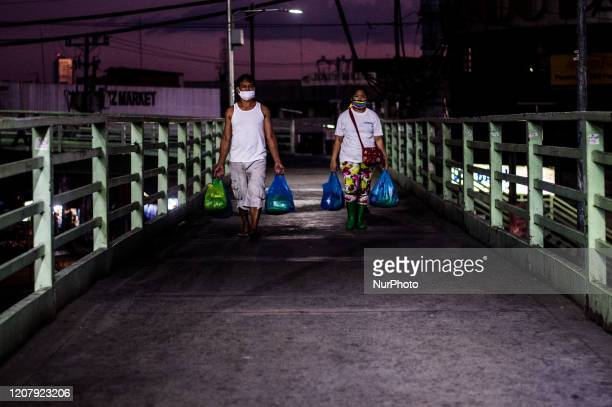 Vendors wearing protective face masks pass through a pedestrian overpass, leaving the market before the curfew in Quezon City, Philippines on March...