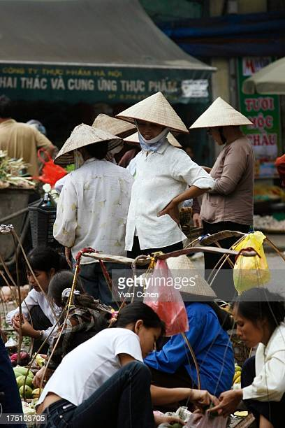 Vendors wearing traditional conical hats in the bustling Dong Xuan market area in Hanoi's old quarter Hanoi is Vietnam's administrative capital and...