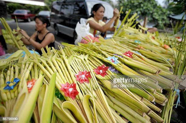 Vendors weave palm branches into decorative creations in preparation for 'Palm Sunday' on a Manila sidewalk on April 4 2009 Lenten Sunday in this...