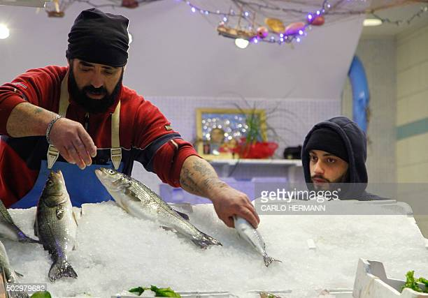 Vendors work at the traditionally fish market open all night long before the New Year Eve in downtown Naples on December 30 2015 / AFP / CARLO HERMANN