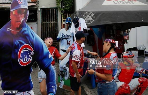 Vendors working a booth full of Red Sox gear joke with one another as they set up cardboard cutouts of famous Puerto Rican baseball players before...