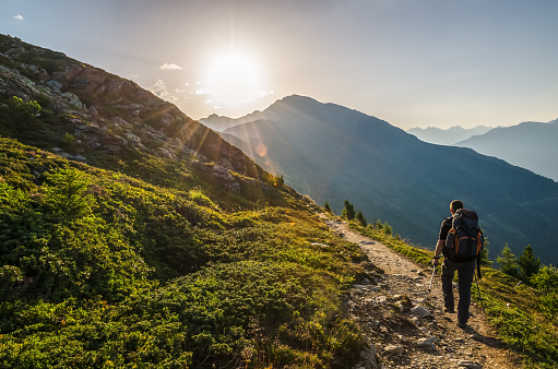 Venetberg, Austria - August 02 2017: Single hiker in the early morning at sunrise on a trekking path in the Lechtaler Alps 1054012932