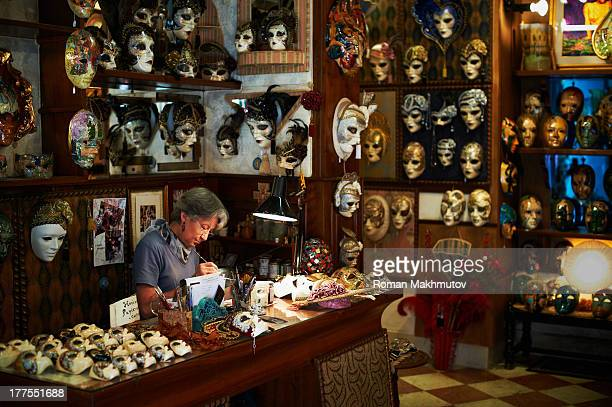 Venetian mask maker in his workshop and trade shop. Venetian masks hanging on walls around her.