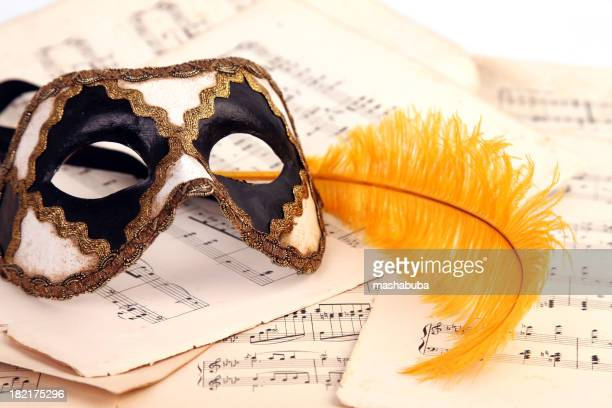 Venetian mask, notes and feather.