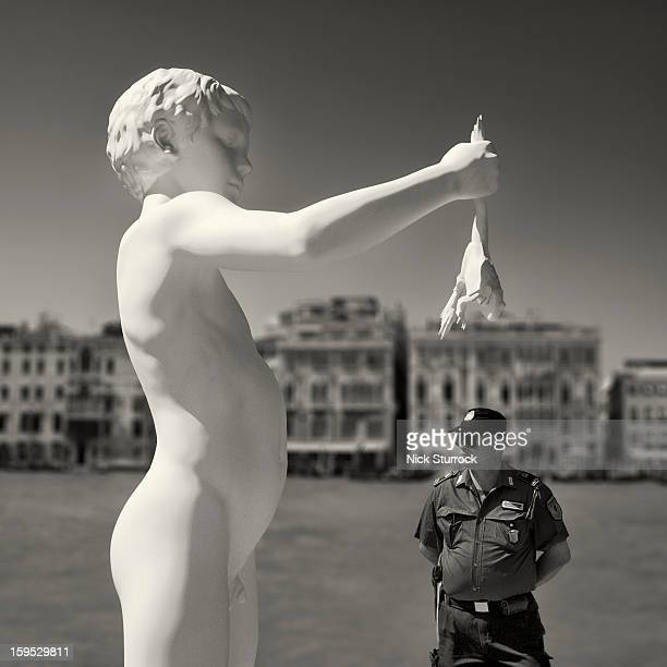 Venetian policeman patrols beneath a giant statue of a boy holding a frog on the banks of the Gran Canal