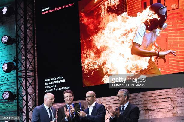 Venezualan AFP photographer Ronaldo Schemidt holds his award next to contest officials Lars Boering Prince Constantijn of the Netherlands and Burhan...