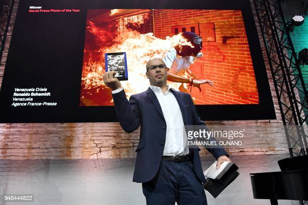 TOPSHOT Venezualan AFP photographer Ronaldo Schemidt holds his trophy in Amsterdam on April 12 2018 during the 2018 World Press Photo award ceremony...