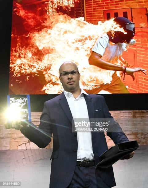 Venezualan AFP photographer Ronaldo Schemidt holds his trophy in Amsterdam on April 12 2018 during the 2018 World Press Photo award ceremony after...