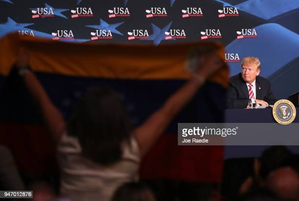 Venezuela flag is held up as US President Donald Trump attends a roundtable discussion about the Republican $15 trillion tax cut package he recently...