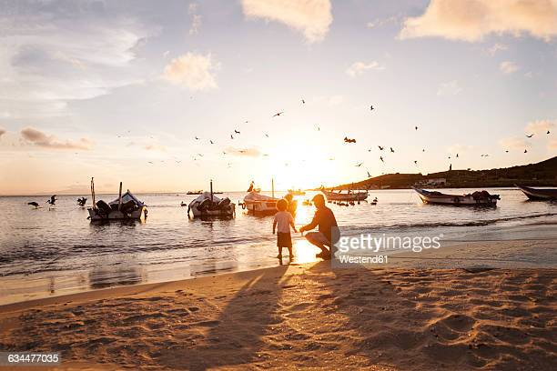 Venezuela, Isla Margarita, Juan Griego, little boy and his grandfather at seafront by sunset
