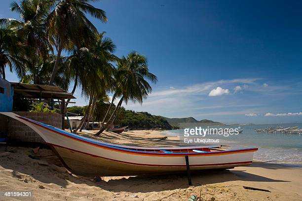 Venezuela Margarita Island Playa la Galera Boat on the tropical beach just in front of a small house and palm trees while other boats are noticeable...