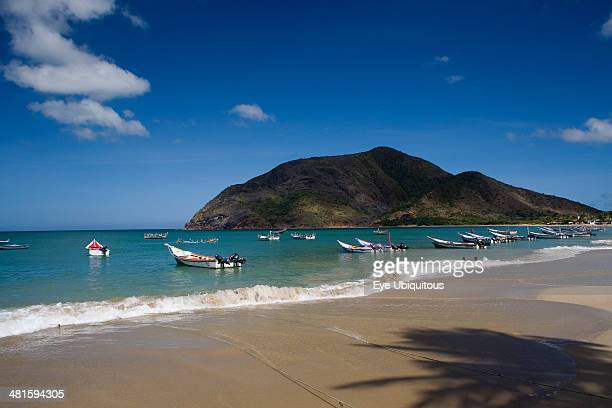 Venezuela Margarita Island Playa la Galera View of exotic beach with palm trees and their shades on the sand just in front of fishing boats floating...