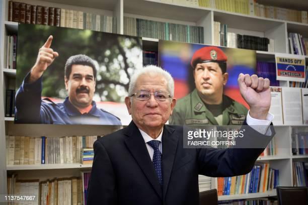 Venezuela Permanent representative to the United Nations in Geneva Ambassador Jorge Valero poses between photographs of President Nicolas Maduro and...