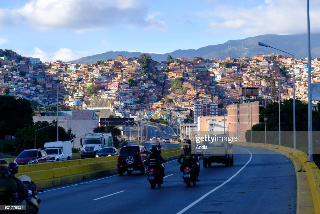 GuzmÌÁn Blanco shanty towns in the upper city and members of the National Guard riding motorbikes on the road.