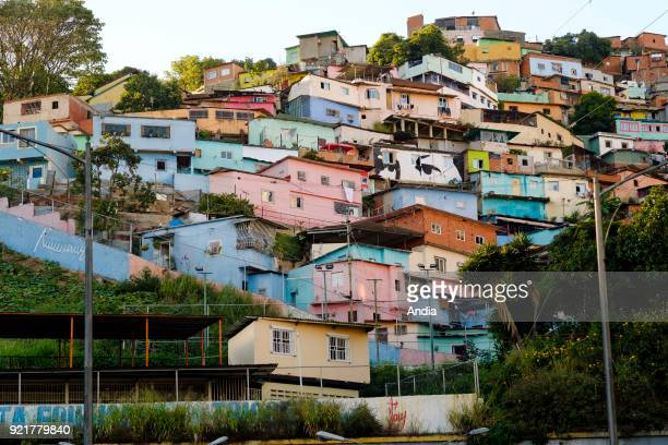 shanty towns in the upper city with a mural depicting 'the eyes of Hugo Chavez' campaign poster used by Maduro in memory of Chavez's Bolivarian...