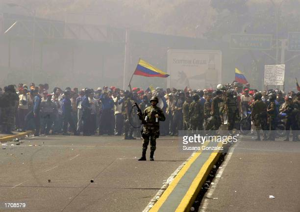 Venezuela soldier stands ready with a tear gas gun while standing in front of supporters of Venezuelan President Hugo Chavez January 3 2003 in...
