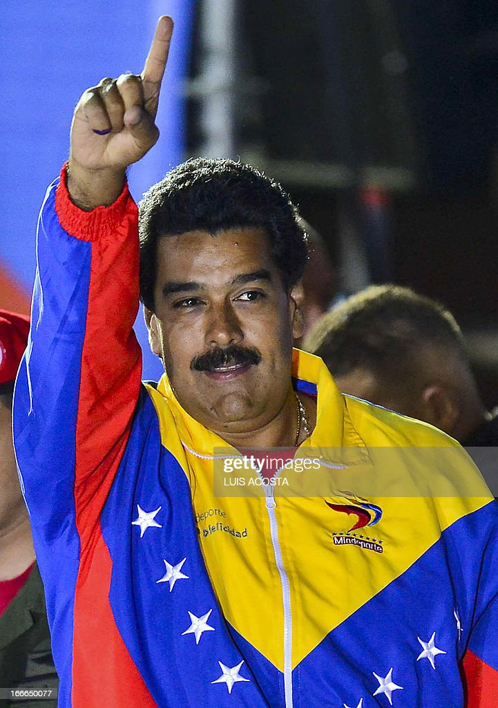 Venezuelan acting President Nicolas Maduro waves after knowing the election results in Caracas on April 14, 2013. Venezuela's acting President Nicolas Maduro declared victory on Sunday in the race to succeed late leader Hugo Chavez after the electoral council announced that he had won in a close battle. AFP PHOTO/Luis Acosta