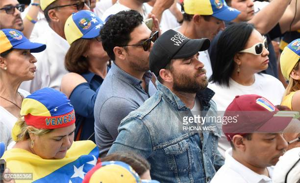Venezuelan actor Alejandro Nones prays as he participates in a rally against the Venezuelan government in front of the Freedom Tower in Miami Florida...