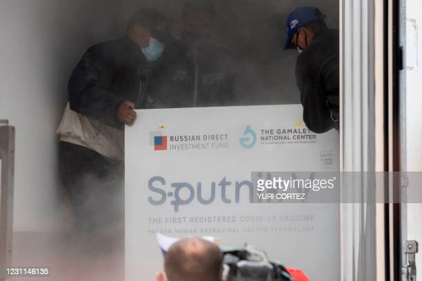 Venezuelan airport workers place in a refrigerated truck packages containing 100,000 doses of the Russian Sputnik V vaccine against the COVID-19...