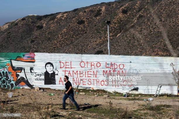Venezuelan artist Manuel Oliver father of slain Joaquin Oliver walks near his mural on the USMexico border fence reading On the other side they also...