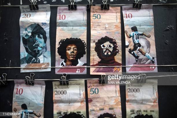 Venezuelan bills painted by Venezuelan migrants Javier Ceballos and Paula Villamizar re displayed for sale in a street in Bogota Colombia on May 3...