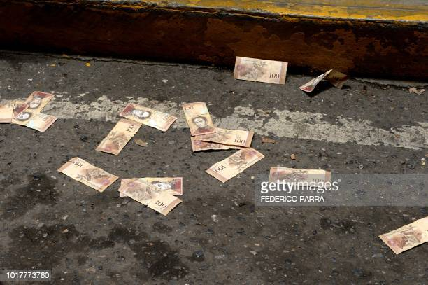 Venezuelan Bolivar banknotes remain on the pavement during after being thrown by health workers during a protest for the lack of medicines, medical...