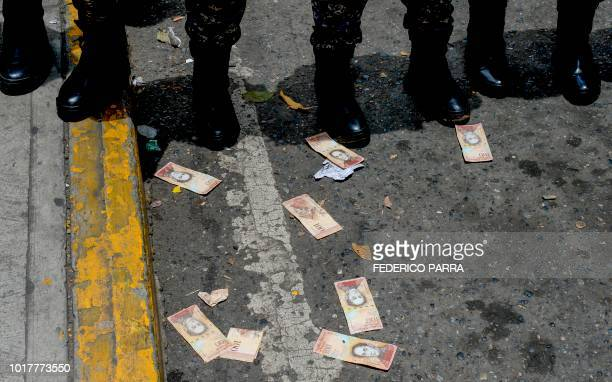 Venezuelan Bolivar banknotes remain on the pavement in front of a line of police officers during a health workers protest for the lack of medicines,...