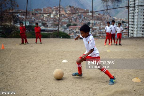 A Venezuelan boy attends football classes at the San Jose de Calasanz School in Catia neighborhood in Caracas on June 11 2018 In Catia birthplace of...