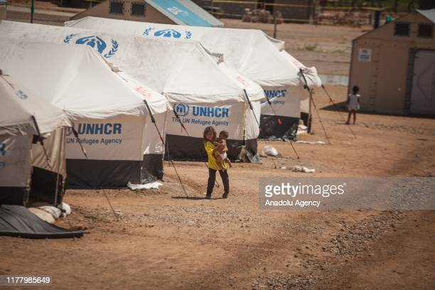 Venezuelan child carries her brother while she walks near the tents at UNHCR camp in Maicao, La Guajira, Colombia, on October 24, 2019. Around...