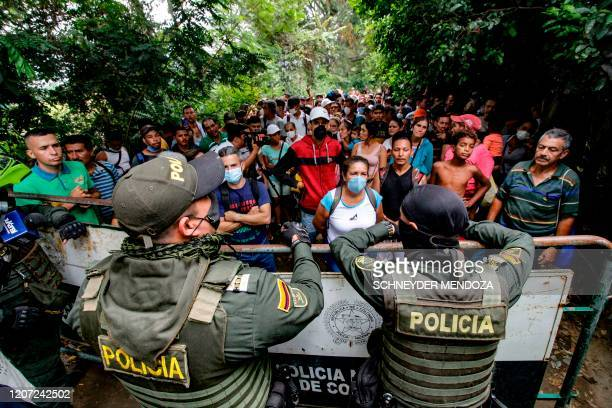 Venezuelan citizens try to enter Colombia while wearing protective face masks to prevent the spread of Coronavirus, in Cucuta, Colombia, on March 15,...