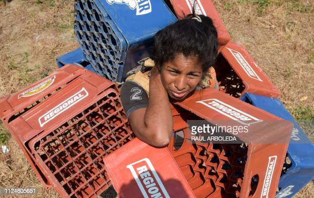 Venezuelan Dayana Pirela carries empty soda and beer crates to sell after crossing from Venezuela through 'Trochas' illegal trails near the Simon...